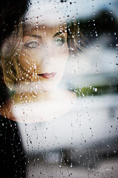 Porträtfoto Frau hinter nasser Scheibe - verträumt