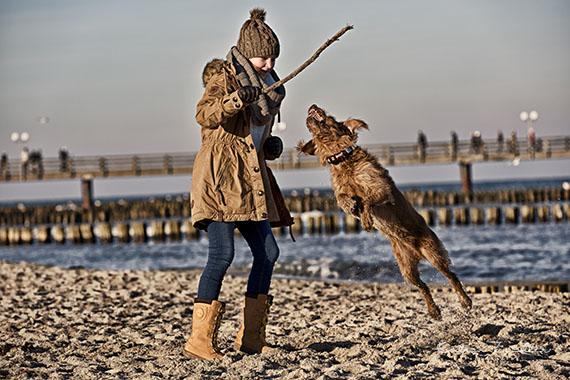 Kinderfotografie - Kind spielt mit Hund am Strand
