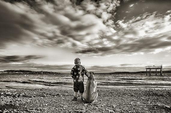 Kinderfotografie - Kind steht mit Hund am Strand
